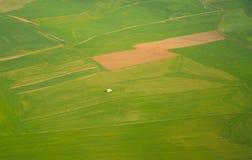 Luchtmening van een eenzaam huis onder gebieden, percelen landbouwgrond Stock Foto's