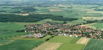 Luchtmening van een klein vliegtuig van een dorp dichtbij Braunschweig met gebieden, weiden, landbouwgrond en kleine bossen in he stock fotografie