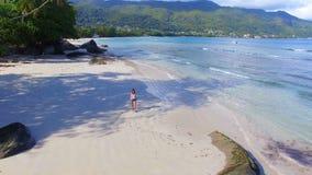 Luchtmening van een mooi meisje die onderaan Beau Vallon Beach 2, Seychellen lopen stock videobeelden