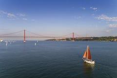 Luchtmening van een mooie zeilboot op de Tagus-Rivier met 25 van April Bridge op de achtergrond, in de stad van Lissabon Stock Foto's