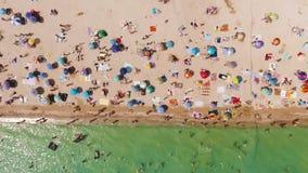 Luchtmening van een overvol strand in een zonnige hete dag Gele zand en paraplu's stock footage