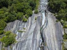 Luchtmening van een waterval in Val di Mello, een groene die vallei door granietbergen en hout wordt omringd Val Masino, Sondrio  Stock Foto's