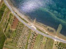 Luchtmening van een weg die langs de Kroatische kust loopt en door landbouwgebieden, met aanplantingen en gecultiveerd F overgaat stock afbeeldingen