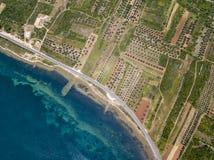 Luchtmening van een weg die langs de Kroatische kust loopt en door landbouwgebieden, met aanplantingen en gecultiveerd F overgaat stock foto