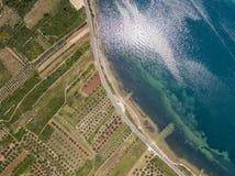 Luchtmening van een weg die langs de Kroatische kust loopt en door landbouwgebieden, met aanplantingen en gecultiveerd F overgaat stock foto's