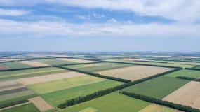 Luchtmening van gebieden met diverse soorten landbouw, tegen bewolkte hemel royalty-vrije stock afbeelding