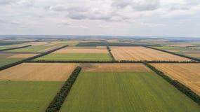 Luchtmening van gebieden met diverse soorten landbouw, tegen bewolkte hemel royalty-vrije stock fotografie