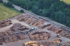 Luchtmening van gestapelde timmerhoutstapels met zware bewegende machines en een spoorwegspoor stock fotografie