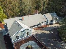 Luchtmening van Groot grijs die huis door bomen wordt omringd Stock Foto