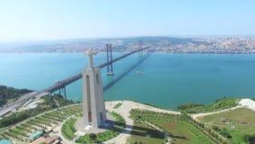 Luchtmening van Heiligdom van Christus de Koning Lissabon overzien en 25 DE die Abril Bridge Lissabon en Almada verbinden stock videobeelden
