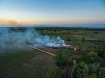 luchtmening van het droge gras van Burning van de hommellandbouwer in zonsondergangtijd, stock fotografie