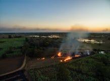 luchtmening van het droge gras van Burning van de hommellandbouwer in zonsondergangtijd, royalty-vrije stock foto