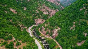 Luchtmening van hommel over bergweg en krommen die door boslandschap gaan stock video