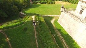 Luchtmening van jong huwelijkspaar die in grepen bij het kasteel dansen 4K stock video