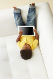 Luchtmening van Jongen op Sofa Playing With Digital Tablet Royalty-vrije Stock Afbeelding