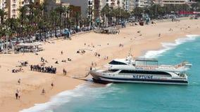 Luchtmening van ` Lloret de Mar `, wanneer een toeristenboot bij het strand aankomt Hypertijdspanne stock video