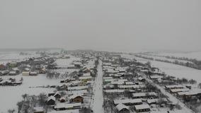 Luchtmening van Oekraïens dorp Bloem in de sneeuw Vlotte vlucht rechtstreeks vooruit stock videobeelden