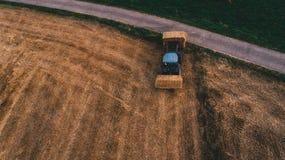 Luchtmening van oogstgebied met rond baal van het tractor de bewegende hooi stock foto's