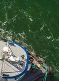 Luchtmening van sleepboot, kabels en arbeiders die te dokken schip bijstaan, Alaska, de V.S. stock fotografie