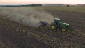 Luchtmening van tractor die de grond op zonsondergang ploegen stock videobeelden