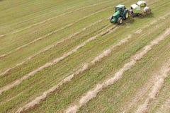 Luchtmening van tractor met ronde pers op gebied Stock Afbeelding