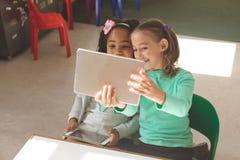 Luchtmening van twee schoolmeisjes die een foto met een digitale tablet nemen stock fotografie