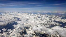 Luchtmening van vliegtuigvenster met blauwe hemel, sneeuwpieken en witte wolken stock videobeelden