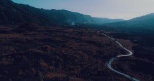 Luchtmening van vulkanisch rotsachtig landschap met weg in Bali stock videobeelden