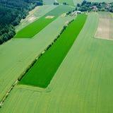 Luchtmening van weide op weg en landbouwgebieden met bos Stock Afbeelding