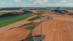 Luchtmening van windturbines en windgernerators in motie op een de zomersdag over tarwegewassen met met grote open hemel stock footage