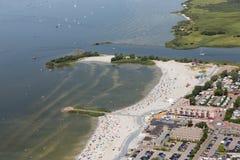 Luchtmenings Nederlands dorp Makkum met strand en zwemmende mensen stock foto's
