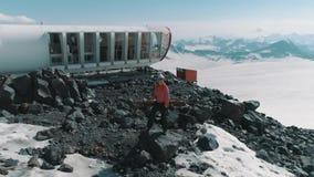 Luchtmeningsvrouw die op stenen bij sneeuwbergen mooi landschap dansen stock videobeelden