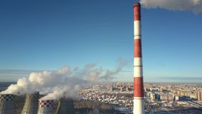 Luchtmotie voorbij schoorsteen en koeltorens tegen stad stock footage