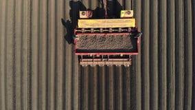 Luchtonderzoek, hoogste mening, grote tractor met speciaal materiaal om potatosritten door geploegd gebied van zwarte te planten stock footage