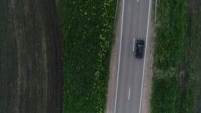 Luchtonderzoek zwarte auto die zich langs de weg bewegen Hoogste mening stock videobeelden