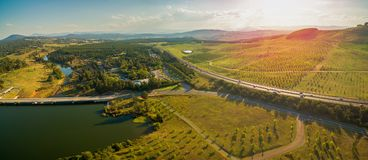 Luchtpanorama die van Tuggeranong-Brede rijweg met mooi aangelegd landschap dichtbij de Nationale Arboretum en Meergriffioen van  stock afbeelding