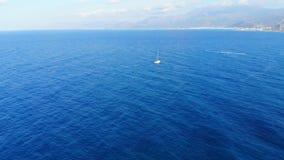 Luchtpanorama op blauwe overzees en klein wit jacht die, Kreta, Griekenland weg varen stock footage