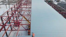 Luchtschot Het schieten van de lucht In het kader van de arbeiders zijn bouwers, opzetten het dak van de productie stock videobeelden