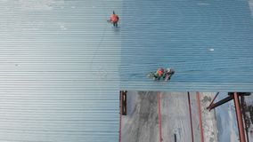 Luchtschot Het schieten van de lucht In het kader van de arbeiders zijn bouwers, opzetten het dak van de productie stock footage