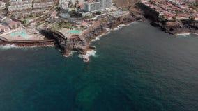 Luchtschot Toeristenstad met vele hotels en pools op de kusten van de Atlantische Oceaan De golven raken vulkanisch stock footage