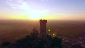 Luchtschot, Upezzinghi-toren op de rotsachtige die dagzomende aardlaag in Italië, Toscanië, op het zonsonderganglicht, met hommel stock footage