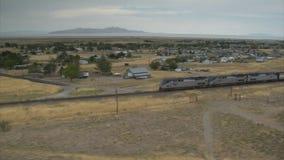 Luchtschot van amtraktrein en woestijnstad met Great Salt Lake stock videobeelden