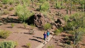 Luchtschot van Woestijnwandelaars op Lang Dusty Trail stock videobeelden