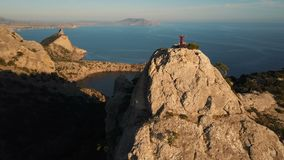 Luchtsilhouet van een jonge vrouw die tot de bovenkant van een berg tegen het overzees bij zonsondergang beklimmen Dame op de top stock videobeelden