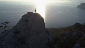 Luchtsilhouet van jonge vrouw op de bovenkant van een berg in mooi landschap boven het overzees Dame op top het opheffen stock videobeelden