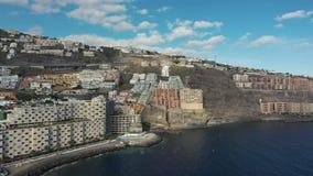 Luchttoevluchtstad op cascade rotsachtige heuvels bij stille oceaan stock video