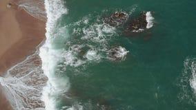 Luchttop down mening van de oceaangolven die het zandige strand en de rotsen in de Middellandse Zee raken stock videobeelden