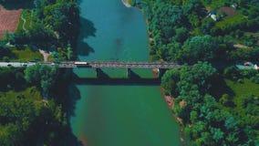Luchtuitzoomenmening van verkeer op een brug over groene rivier 4K stock video