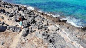 Luchtvlieg rond jonge vrouw status op overzees strand, Griekenland, Kreta stock video