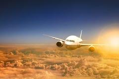 Luchtvliegtuig die over wolk scape en zonlicht erachter vliegen Stock Foto's